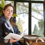 woman sitting reading in a too hot conservatory
